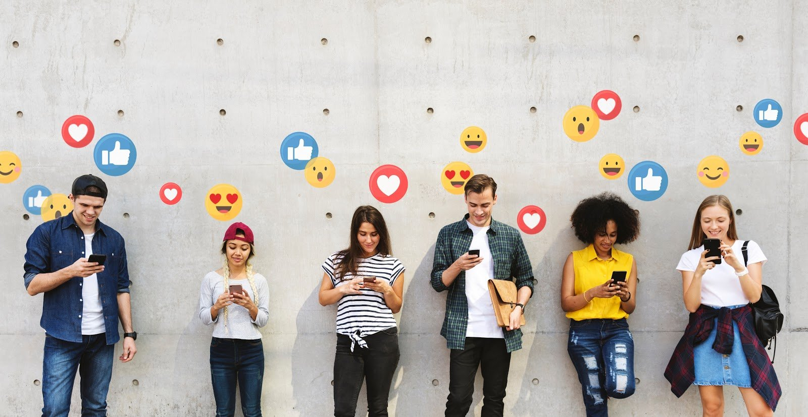 People lean against a wall using their phones with emojis floating above their heads.