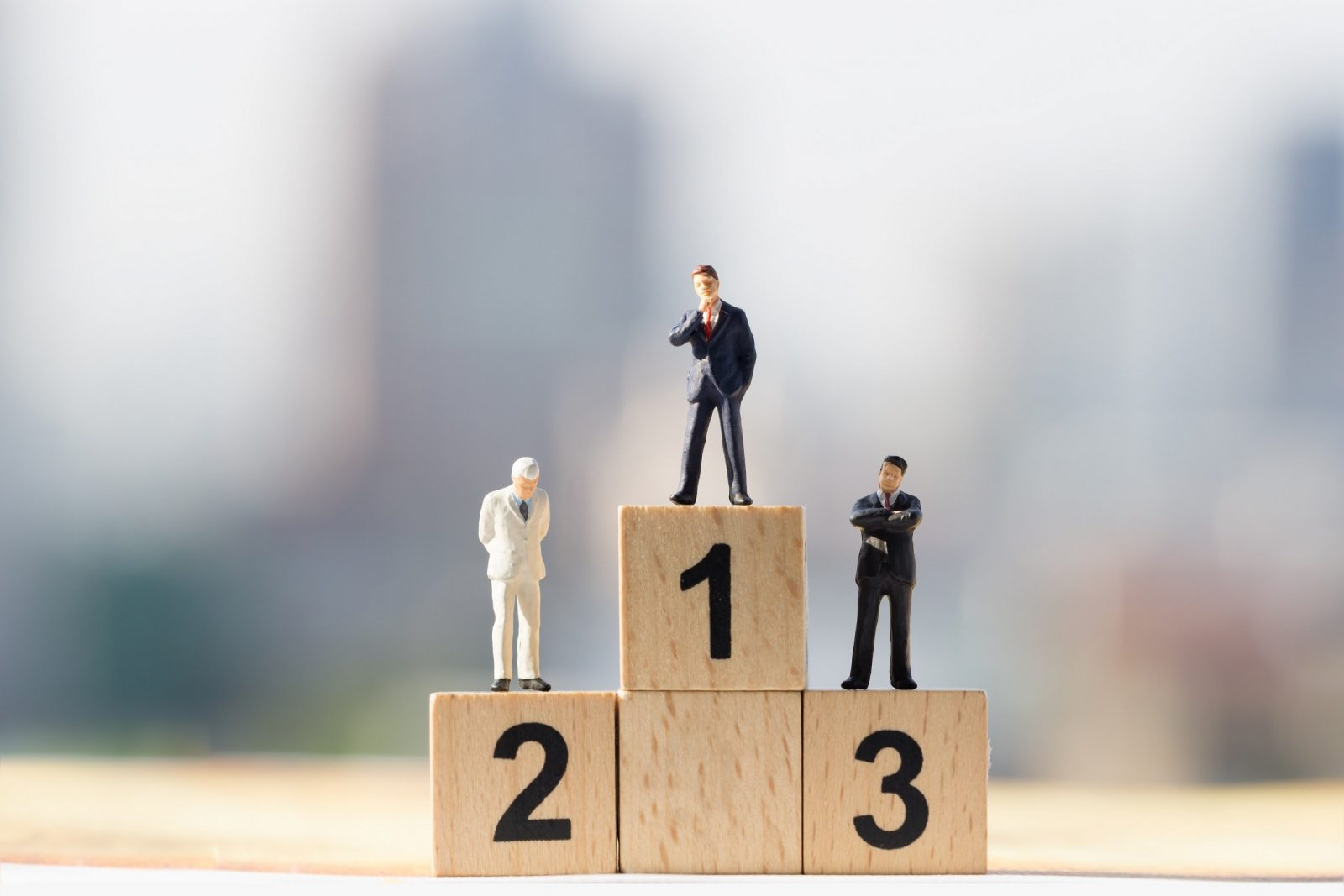 Three figurines sit atop blocks numbered one through three to show each person's ranking.