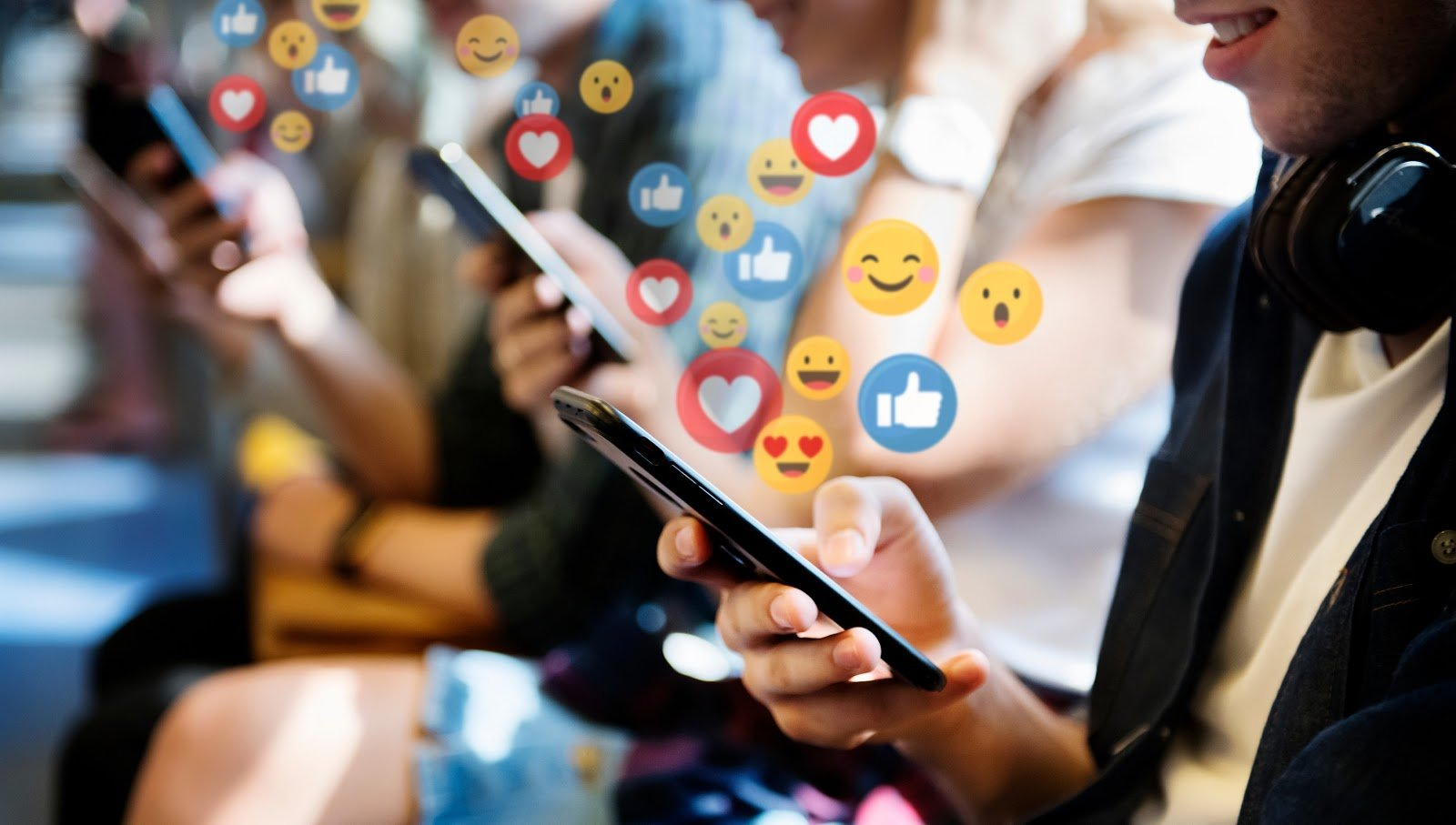 A line of people using their phones with various emojis and reaction icons floating above them.