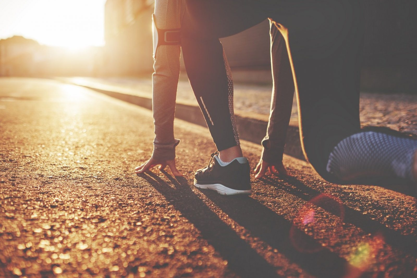 A woman crouches on the pavement ready to begin running as the sun begins to rise.