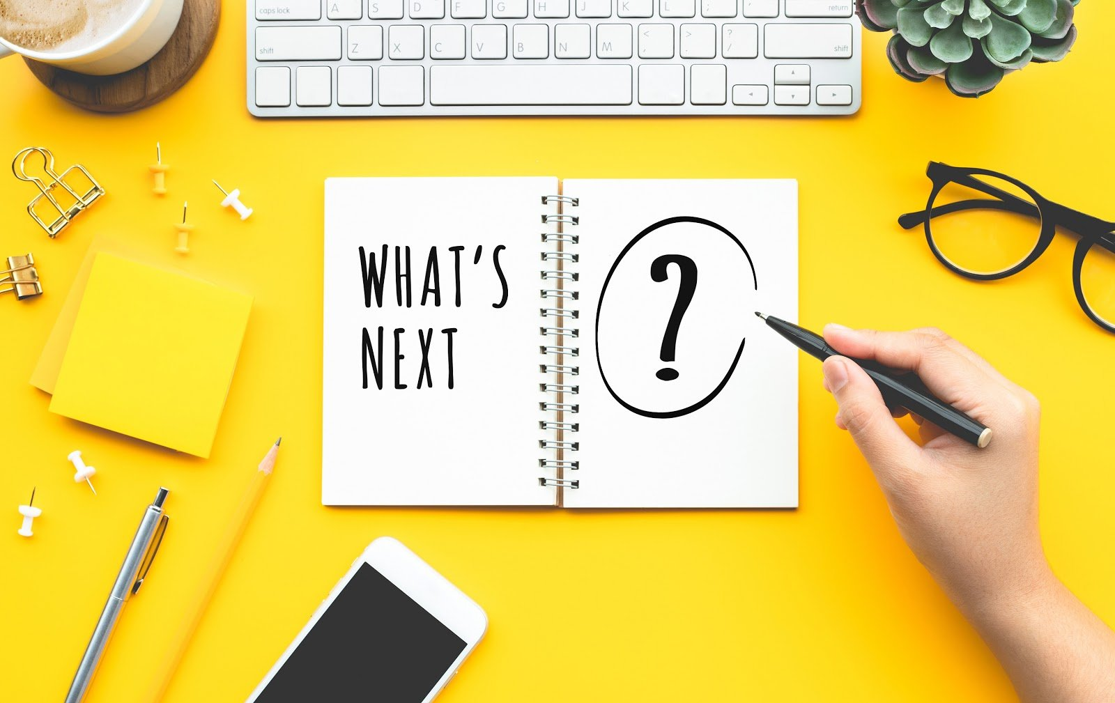 """A keyboard, glasses, a cell phone, sticky notes, thumbtacks, and other items surround a notebook reading """"What's Next?"""" on a bright yellow background."""