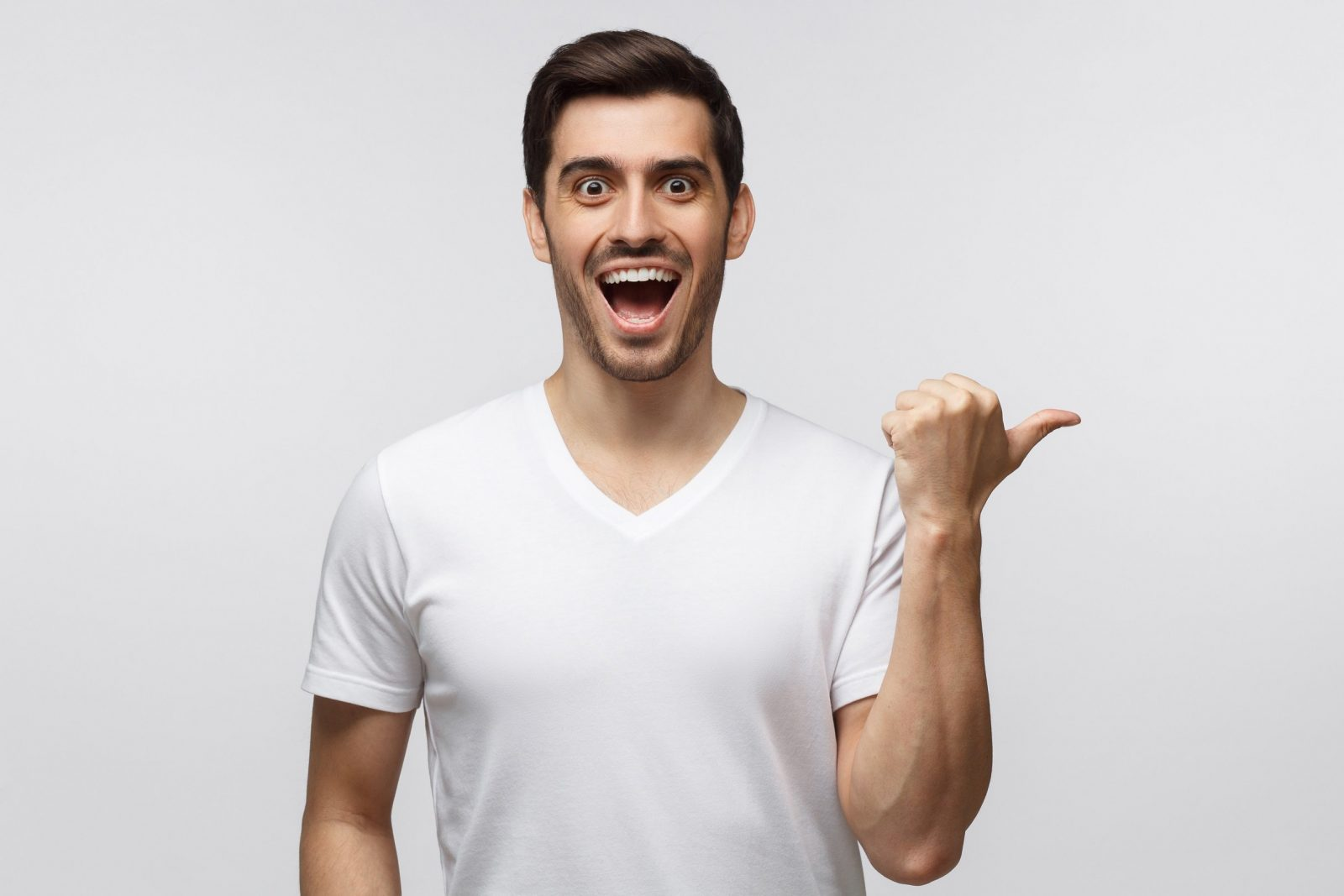 Young surprised man in white t-shirt pointing right with his finger