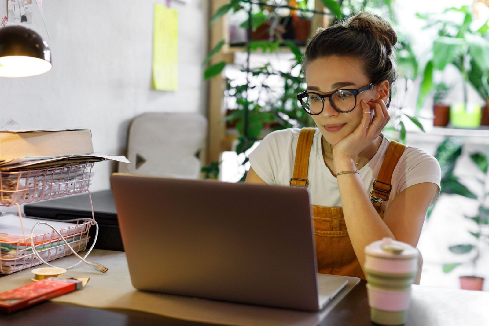 Young female in glasses using laptop to write an article