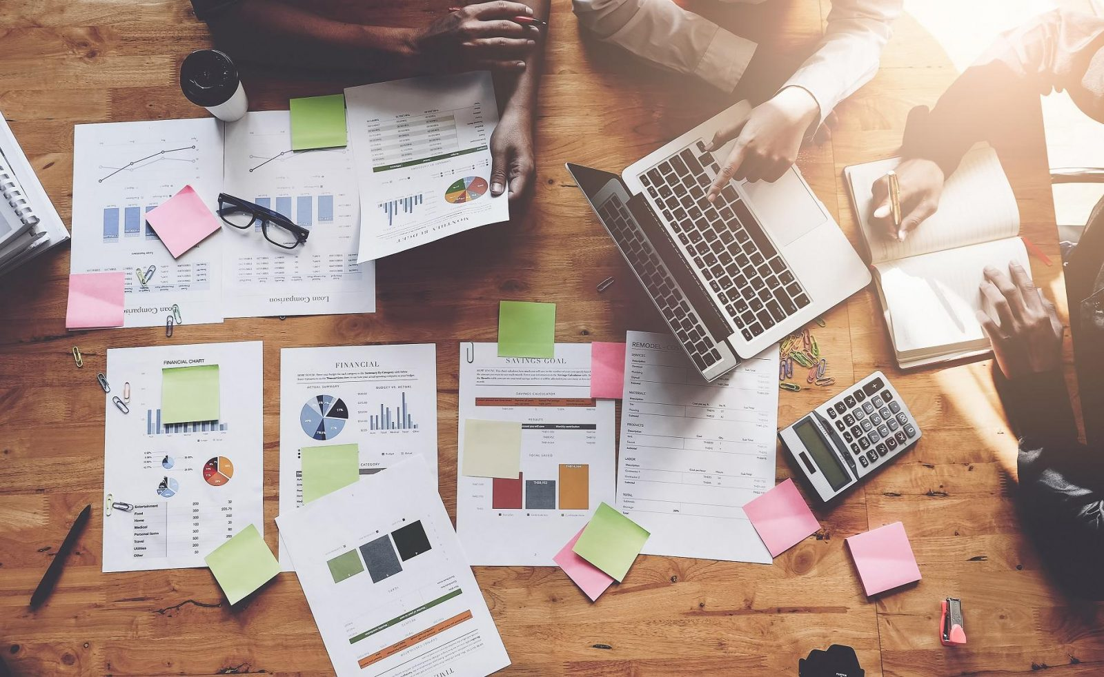 People work around a table that is strewn with papers containing graphs, charts, and spreadsheets, along with sticky notes, a laptop, a calculator, and various other objects.arious other objects